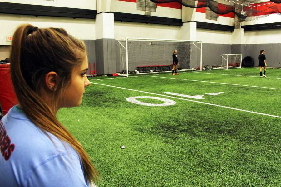 Salls looks on from the sidelines while her teammates train. She will play soccer next year at the University of Central Oklahoma, located outside of Oklahoma City.