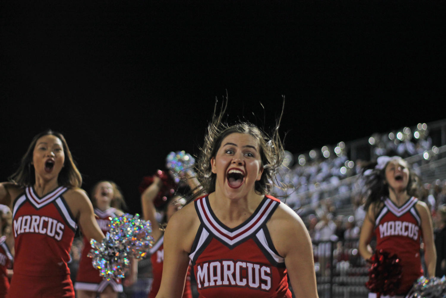 Varsity cheerleaders jump in celebration as Marcus makes a touchdown.