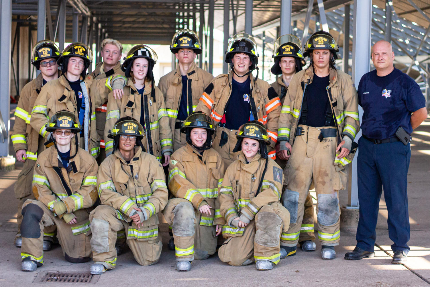 The firefighting program gathered for a group photo after practicing forcible entry, which included multiple ways to pry open an almost 300 pound door jammed with pieces of wood.