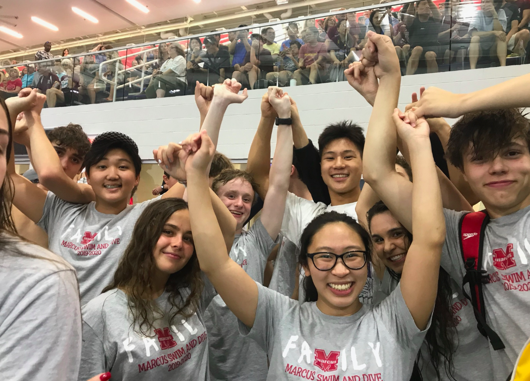 The swim team holds pinkies as they wait for the shootout to begin. At the beginning of big races, the athletes will join together in anticipation and support of their teammates.