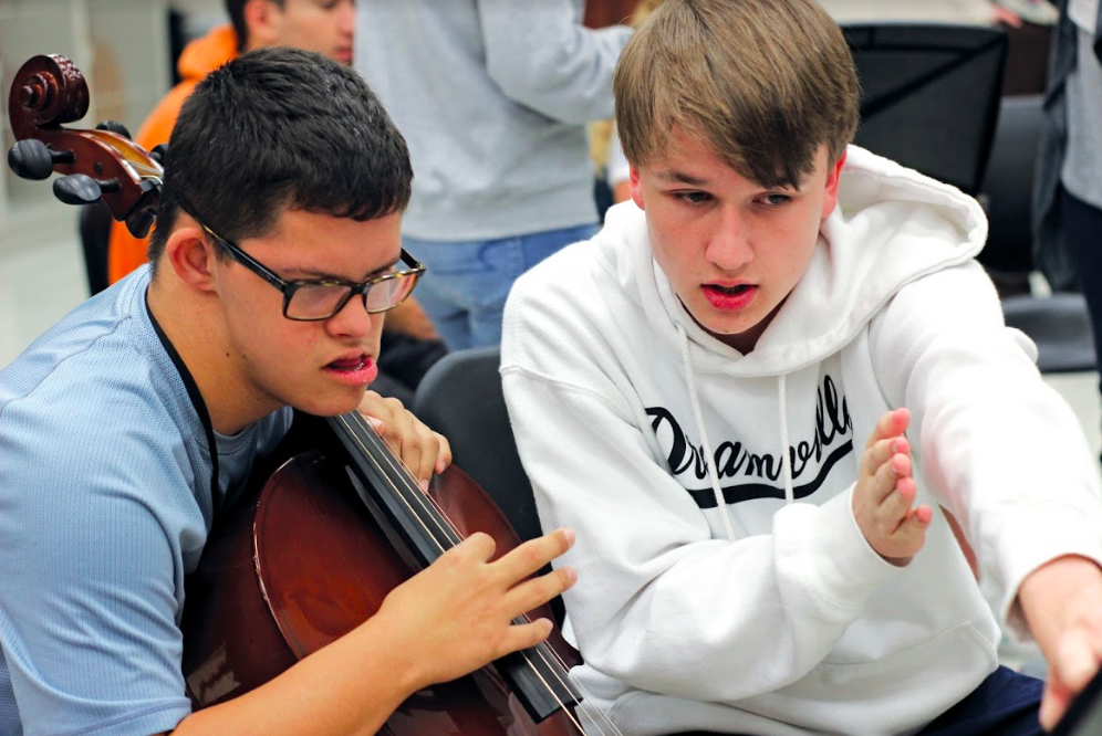 Sophomores Landon Faulkner and Charles Payton read sheet music together. Peer mentors take a leadership role teaching them the fundementals of this skill.