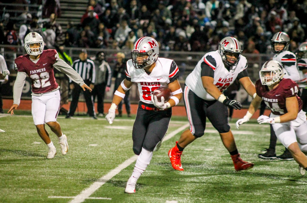 Senior running back Ty'son Edwards is alert of the Lewisville players around him as he runs with the ball. Last season, the Marauders lost the game 17-14 at home, so the team was especially driven to win the annual game this year.