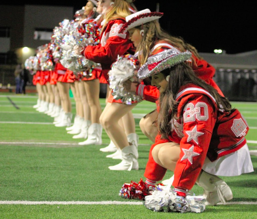Senior Marquette officer Bella Fortino crouches down during their performance. The rest of the Marquettes follow her lead and get in the same position, moving down the line.