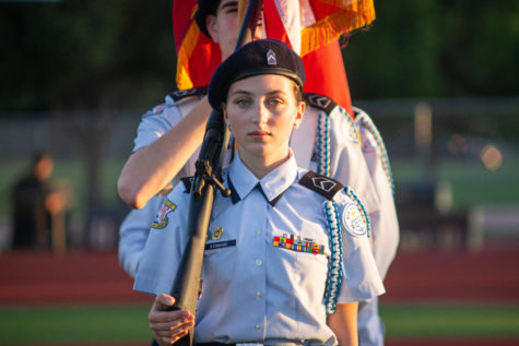 Senior Emma Eidmann presents the colors alongside other AFJROTC students, representing the Marauders prior to the Homecoming football game.