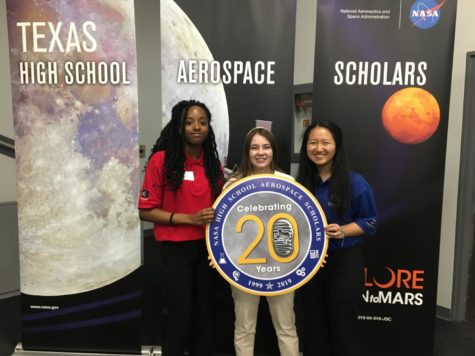 Senior Carol Anne Starks (middle) holds a sign with two other students attending the High School Aerospace Scholars program at the NASA facility in Houston, TX. Carol Anne's 10-person group was tasked with studying the geography of Mars.