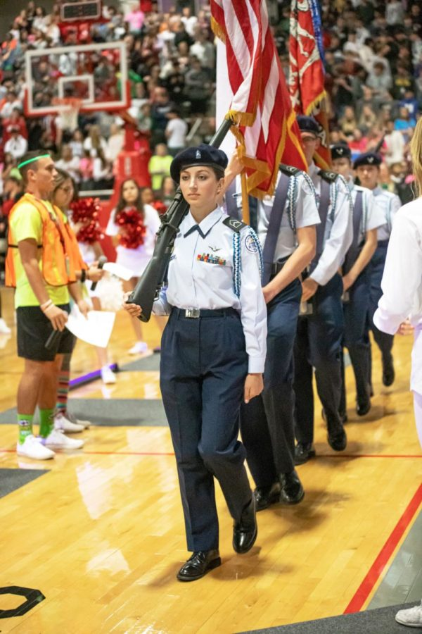Senior Emma Eidmann holds the rifle as she marches with fellow AFJROTC cadets in the Battle of the Axe pep rally. She represents her school during the presentation of the flags at many pep rallies and football games.