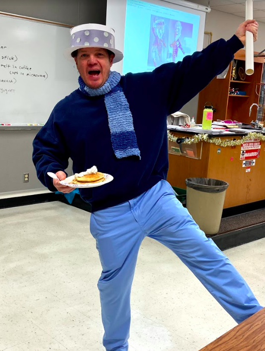 "AP Biology teacher Scott Hinsley enjoys pancakes made by his first period class while dressed as Snow Meiser from ""A Year Without a Santa Claus"" for a holiday spirit day. The pancakes were made with yeast that Hinsley's class grew over several weeks by using flour and water."