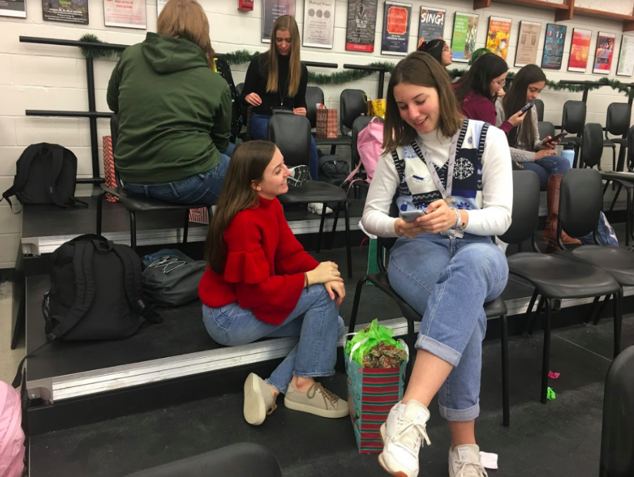 Choir students and juniors Tori Petersheim and Maddie Felan open their candy themed secret Santa gifts. Choir does an annual  gift exchange where students give presents to fellow choir members, according to themed days.