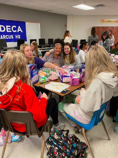 The girls' basketball team and volleyball team participate in a packaging event to pack menstrual products for She Supply.