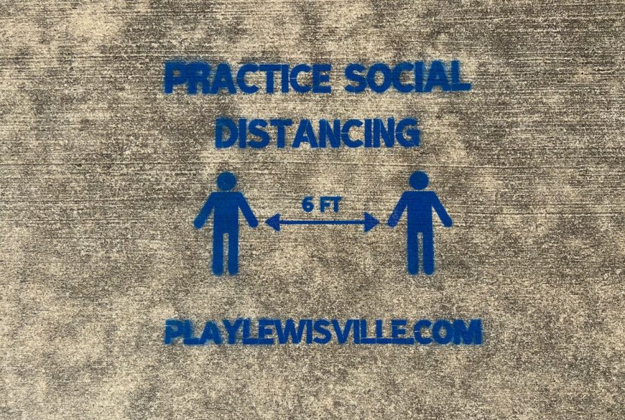 A message promoting social distancing is spray painted on the sidewalk in Leonard L. Woods Park in Lewisville.