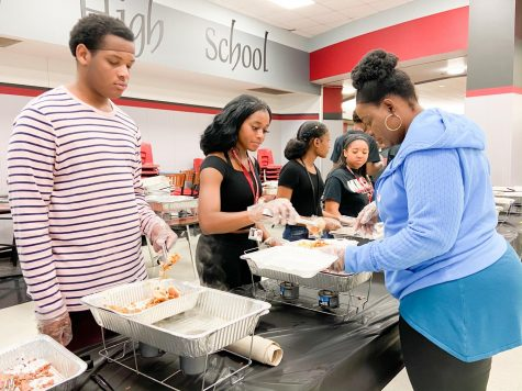Sophomores Phillip Strange and Kim Ume-Ezeoke serve chicken to parent Lola Aje at Taste of Soul on Feb. 28. The event was held by the Black History Club to share traditional soul food with students and staff.