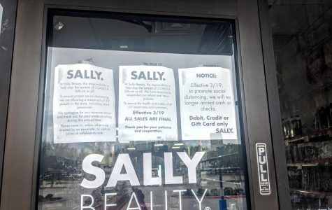 The Flower Mound Sally Beauty Supply posts flyers announcing changes being made due to the COVID-19 pandemic on March 21.