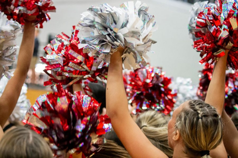 The Marquettes raise their pom poms in the air during a pep rally earlier in the school year. The Marquettes recently decided to postpone their annual spring show and auditions in response to COVID-19.