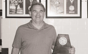 Head cross country, track and field coach Steve Telaneus poses with the girls cross country team's regional trophy in 2016.