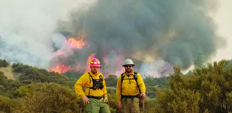 Flower Mound Fire Department Captain Wade Woody and Engineer Brody Eakin wear protective gear in front of the August Complex wildfire. They stayed in California for about two weeks.