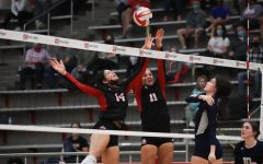 Senior Jazmyn Edmond and junior Maggie Boyd jump to block the ball.