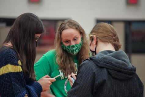 Senior Kaylyn King talks with her friends after signing to swim at the University of North Texas. Athletes signed to play at their respective colleges in the Marauder Gym on Nov. 11.