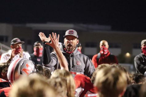 Head Coach Kevin Atkinson celebrates with the team after they secure the win against Plano.