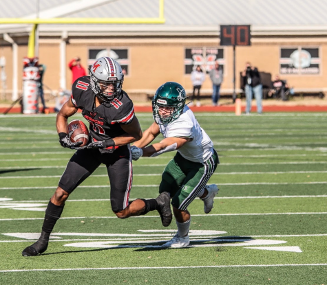 Junior wide receiver and defensive back Dallas Dudley runs through an attempted tackle by a Prosper player.